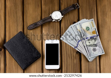 Business concept. Passport, dollars, watch, phone on wooden background - stock photo
