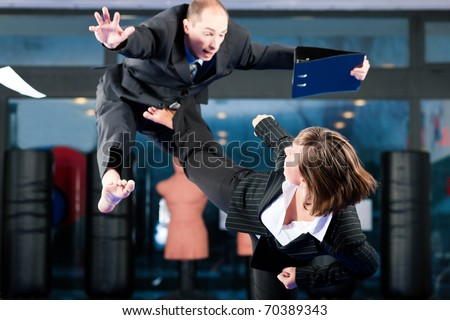 Business concept - People in a gym in martial arts training exercising Taekwondo, both wearing suits - stock photo