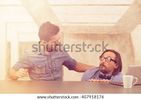 Business concept. Picture of frightened boss hiding under table while his worker explaining about situation in company. - stock photo