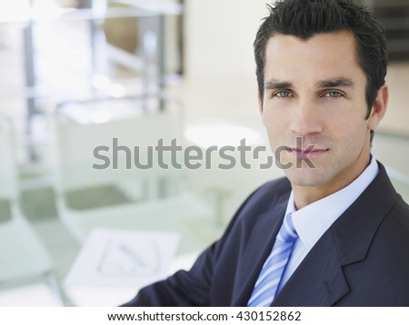 Business concept - Portrait of a happy young businessman, smiling, indoor - stock photo