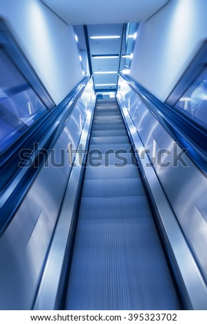 Business Concept shot motion blur of escalator leading up in modern building. perfect background for business related projects
