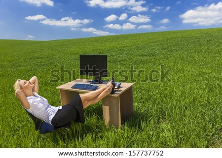 Business concept shot of a beautiful young woman businesswoman relaxing with her feet up at a desk with a computer in a green field with a bright blue sky - stock photo