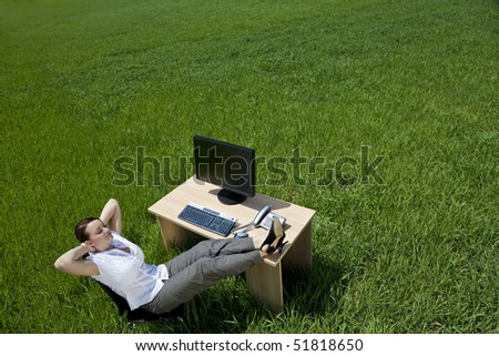 Business concept shot of a beautiful young woman relaxing at a desk in a green field. Shot on location. - stock photo