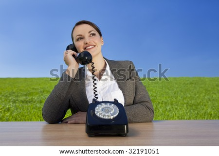 Business concept shot of a beautiful young woman sitting at a desk using an old fashioned phone in a green field with a bright blue sky. Shot on location. - stock photo