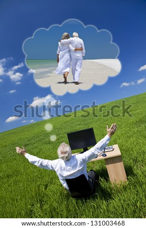 Business concept shot of a senior male executive businessman sitting at work desk in field, arms raised dreaming of tropical romantic beach vacation holiday or retirement with his wife or girlfriend
