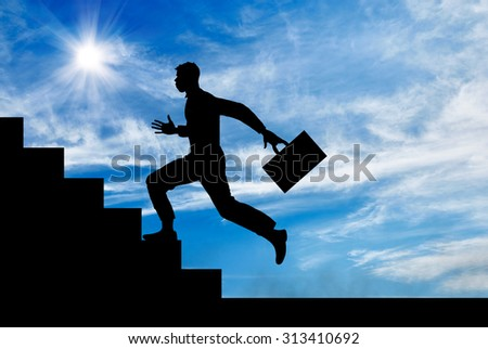 Business concept. Silhouette of a man with a briefcase running up the stairs.