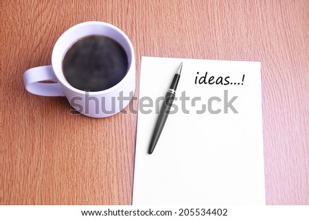 Business Concept - Steamy Coffee And Black Pen With White Paper Listing Ideas On The Table - stock photo