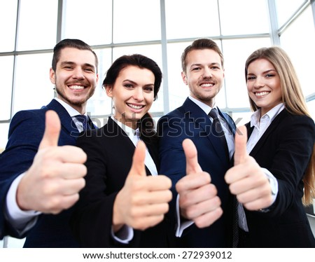 business concept - successful young business people showing thumbs up