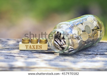 Business Concept - TAXES WORD Golden coin stacked with wooden bar on shallow DOF green background. - stock photo