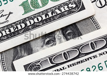 Business concept : three banknotes and Franklin looking from one of them. - stock photo