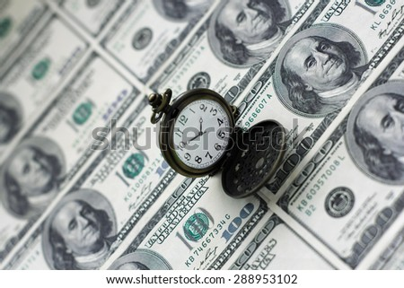 """Business concept """"Time is money"""". Clock over dollars background. - stock photo"""