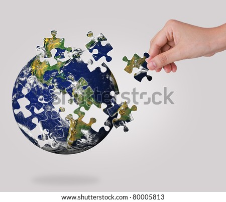 Business concept with a hand building puzzle globe - stock photo