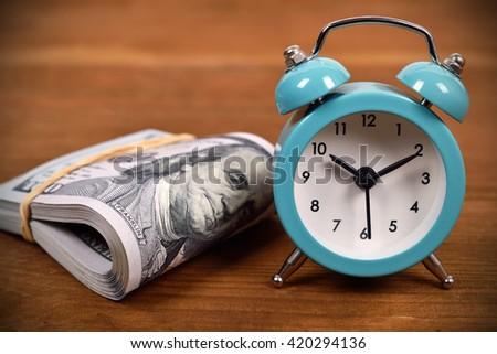 Business concept with dollar and alarm clock on wooden board - stock photo