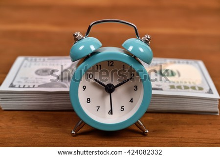 Business concept with dollar and alarm clock on wooden table - stock photo