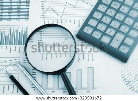 Business concept with magnifying glass, calculator, pen, pencils and financial documents
