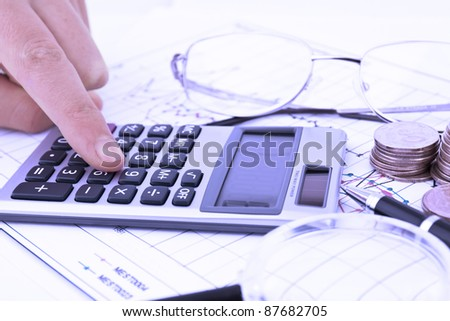 Business concept with notebook, glasses, pen and calculator in blue hue - stock photo