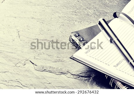 Business concept with paper agenda and pen - stock photo