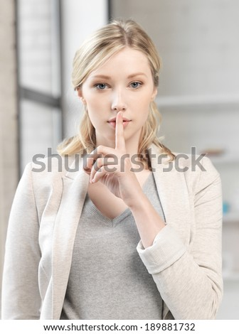 business concept - young woman with finger on lips - stock photo