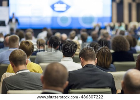 Business Concepts. Large Group of People at the Conference Watching Presentation Charts on Big Board in Front of Them.Horizontal Image Concepts