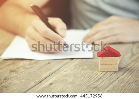 business concepts. Man hand pen and house on wooden table - stock photo
