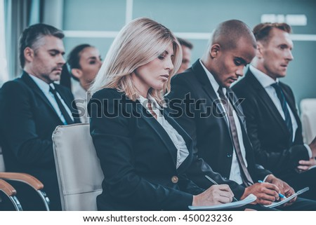 Business conference. Group of business people in formalwear sitting at the chairs in conference hall and writing something gin their note pads