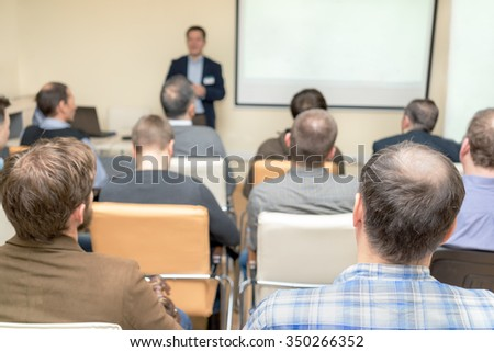 business conference. people sitting rear. teacher near the white board. - stock photo