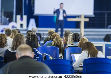 Business Conferences Concept and Ideas. Male Professional Lecturer Speaking In front of the Group of People. Horizontal Image Composition.