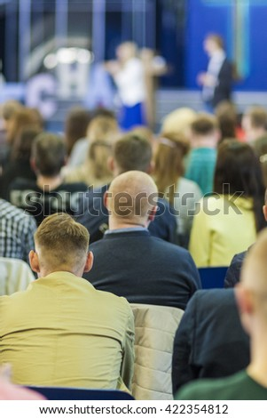 Business Conferences Concepts and Ideas. Two Hosts Speaking In front of the Large Group of People. Vertical Image - stock photo