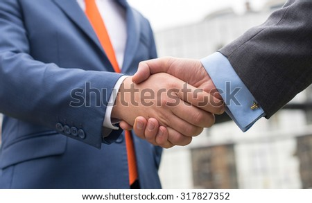 Business confidence. Close up of handshake of two successful businessmen. Outdoors business concept - stock photo