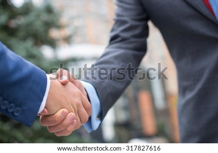 Business confidence. Close up of handshake of two successful businessmen. Outdoors business concept