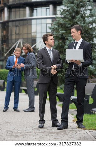 Business confidence. Portrait of motivated businessman in formal suit at work. His business partners are on background. Business outdoors