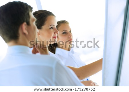 business consultant discussing with colleagues around the flipchart, teamwork - stock photo