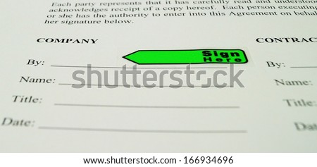 Business Contract Sign the Dotted Line. A sign here flag marks the signature line on a business agreement.  - stock photo