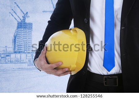Business contractor is holding a safety helmet on blueprint background - stock photo