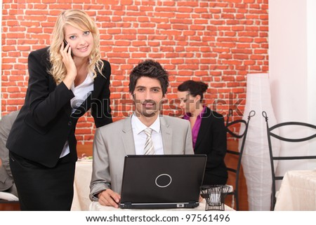 Business couple in a restaurant using a laptop and telephone - stock photo