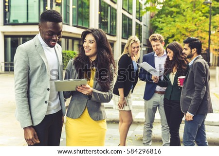 Business couple looking at digital tablet. On background there are some more persons. They all are young, smiling and wearing smart casual clothes. Mixed race group. Teamwork and business concepts.