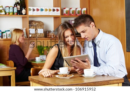 Business couple looking together at tablet computer in a caf�© - stock photo