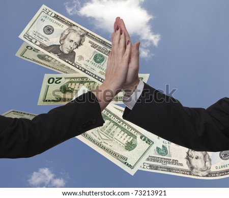 Business couple male and female high five against a blue sky that has American twenty dollar bills fluttering down - stock photo