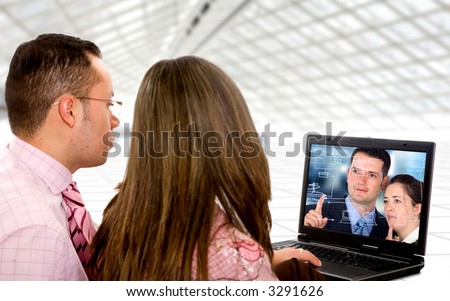 business couple on a laptop in an office environment watching a trainning video - stock photo