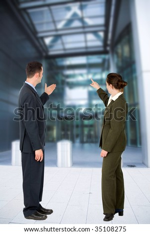 Business couple pointing at a modern building