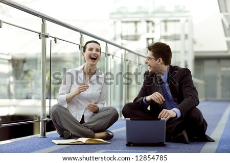 Business couple portrait - young man and woman working together on the floor of modern office corridor