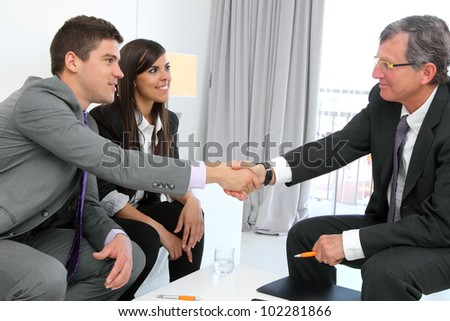 Business couple shaking hands with financial planner. - stock photo
