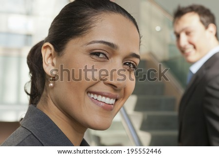 Business couple smiling in modern office building