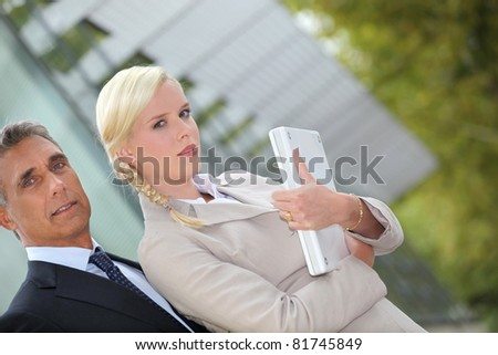 Business couple standing outside with a laptop - stock photo