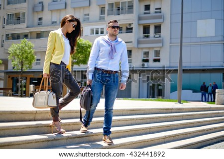 Business couple walking to a meeting down the stairs. Horizontal