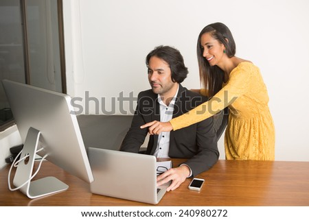 Business couple working at the computer looking at the camera th - stock photo