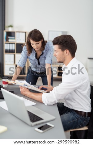 Business couple working on a project together in the office leaning over a desk discussing paperwork in a file, man and woman - stock photo