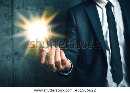 Business creativity concept with elegant adult man holding bright light bulb as metaphor of new ideas - stock photo