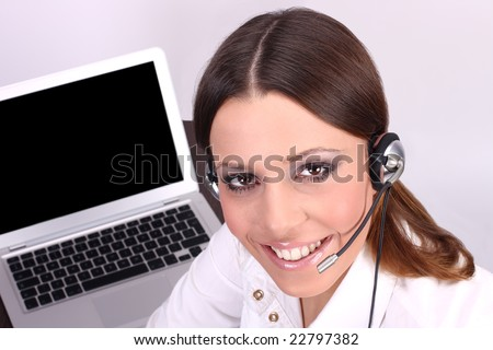Business customer support operator woman with blurred laptop in background. - stock photo