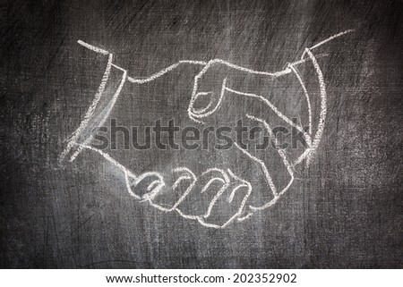 business deal handshake illustrated on a blackboard in white chalk scratched